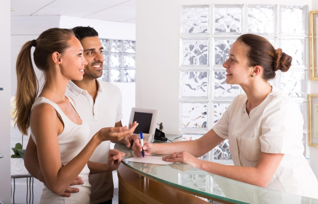 Couple with receptionist at clinic